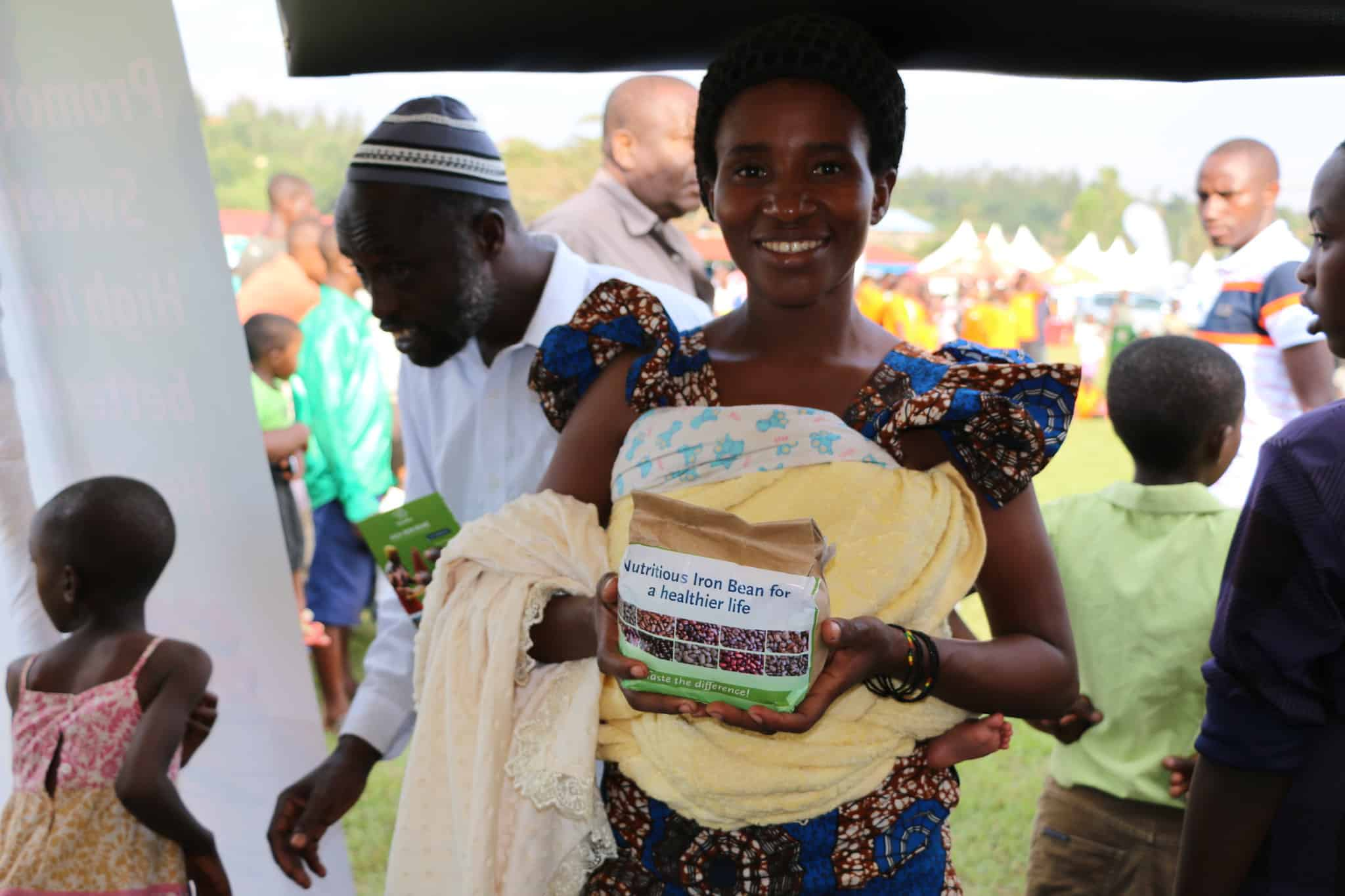 A woman holds a package of iron-biofortified beans at a Rwandan agricultural fair. A new study shows that providing such beans to iron-deficient women in Rwanda improved their ability to perform physical work.