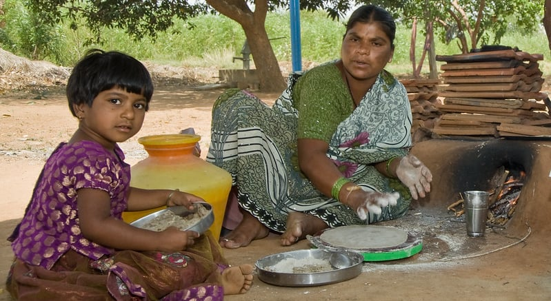 A mother prepares flat bread from pearl millet in Andhra Pradesh, India