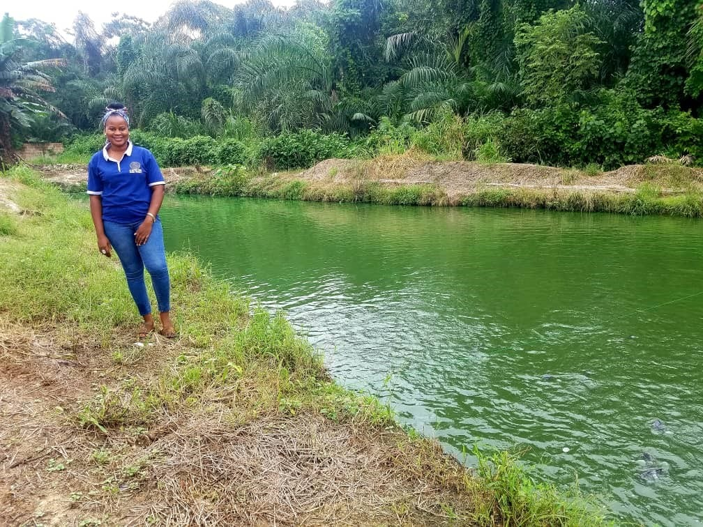 Olubunmi Aderinsola beside a fish pond, in Nigeria. Photo by Worldfish.