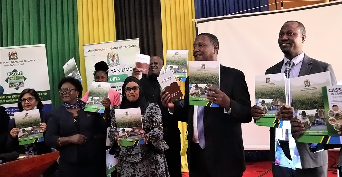 The Honorable Minister and other cassava stakeholders displaying the National Cassava Development Strategy book.