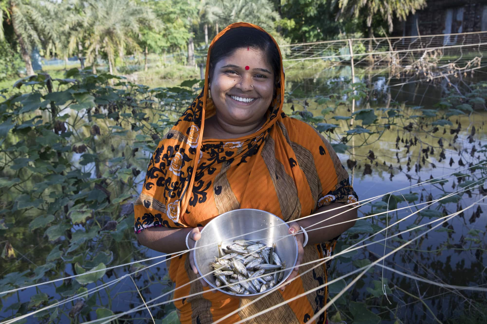 Fish farmer Champa Debnath poses with Mola from her pond in the Khulna District of Bangladesh. Photo by Habibul Haque.