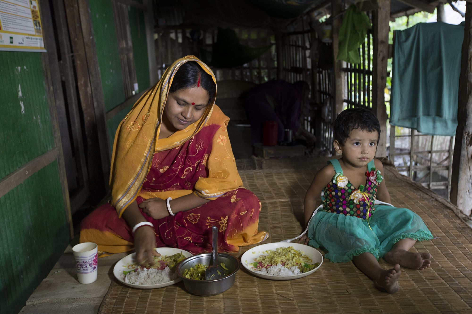 A woman and her daughter eat a healthy meal in Khulna, Bangladesh. Photo by Yousuf Tushar.