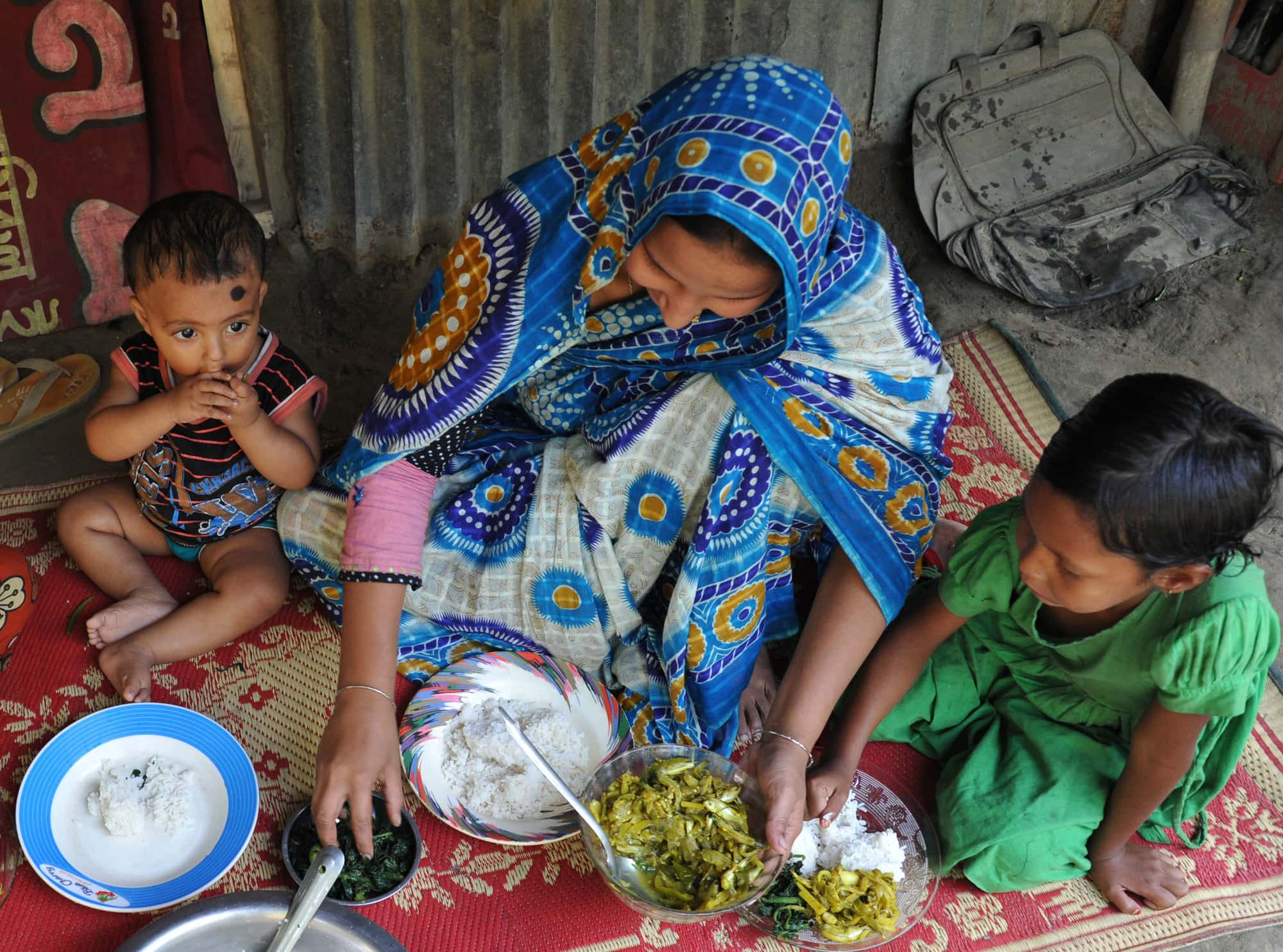A Bangladeshi mother feeding her children nutrient-rich small fish and leafy vegetables. Photo by Finn Thilsted.
