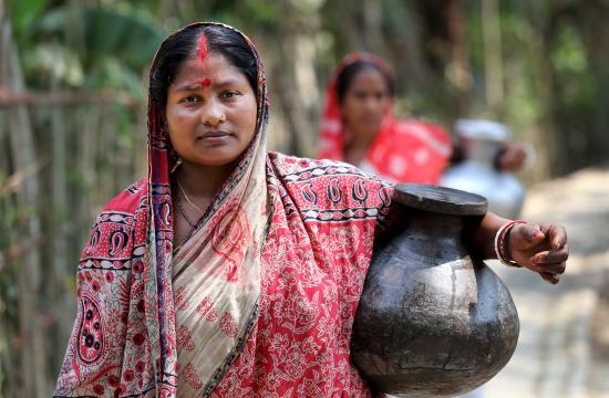 Komola Roy carries drinking water in Fultola Village, Khulna, Bangladesh. Photo by M. Yousuf Tushar.