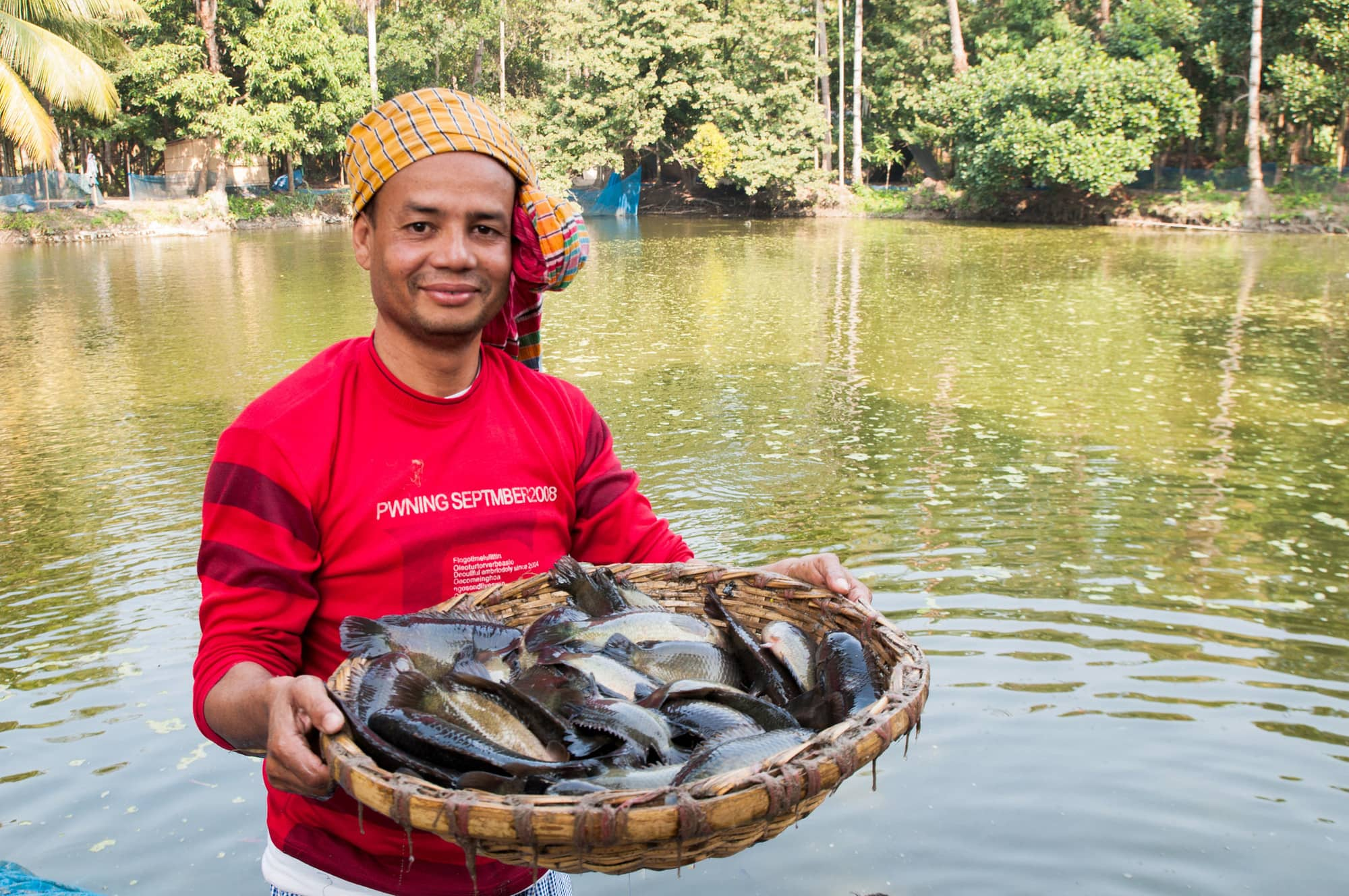 A Bangladeshi farmer poses with the climbing perch fish harvested from his aquaculture pond. The Gates Foundation is in the process of investing in the country's smallholder aquaculture sector. Photo by Balaram Mahalder.