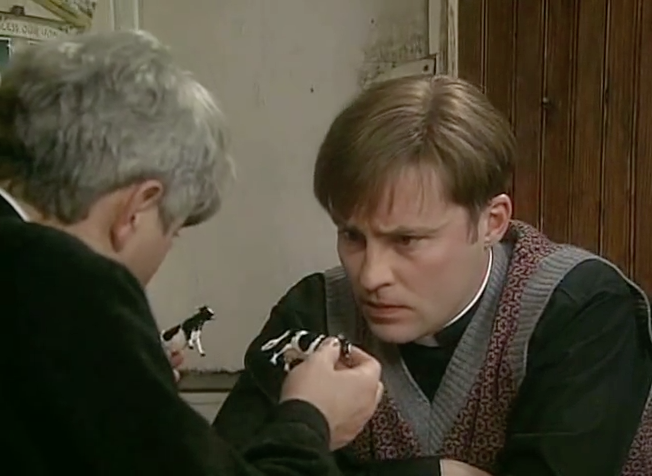 An exasperated Father Ted, a puzzled looking Dougal, and some little cows
