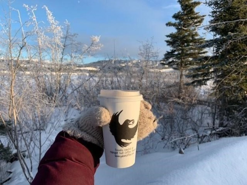 Enjoying a bright beautiful day by the Yukon River with a cup of Midnight Sun's finest