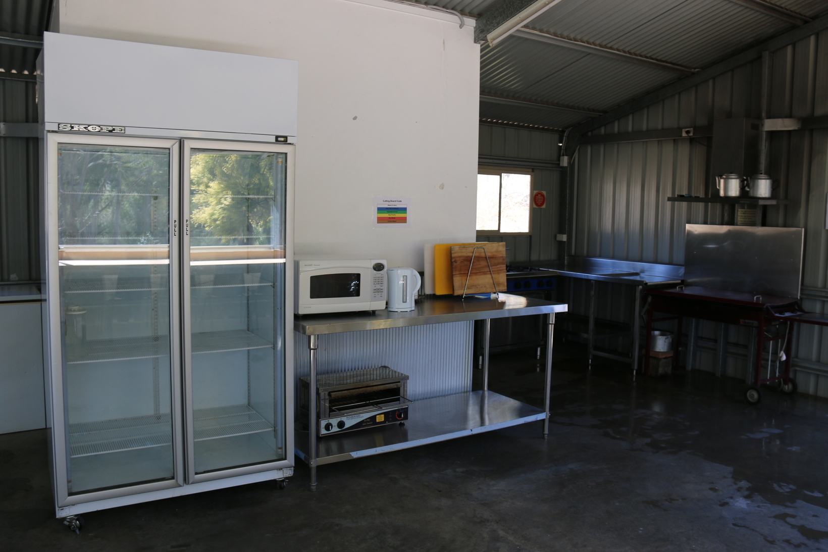 Commercial Fridge, store room with crockery, cutlery, cooking utensils, urn, toaster, microwave, kettle
