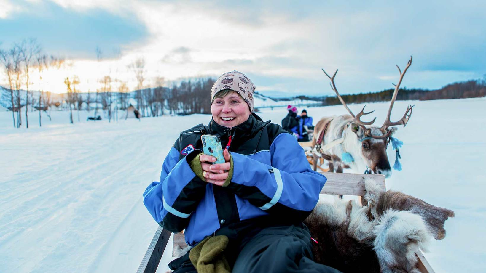 woman holding phone in reindeer sled
