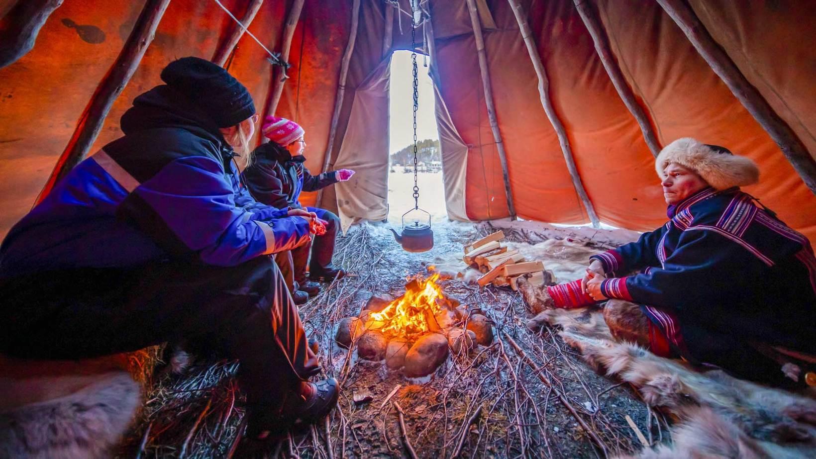 people around a bonfire in a lavvu