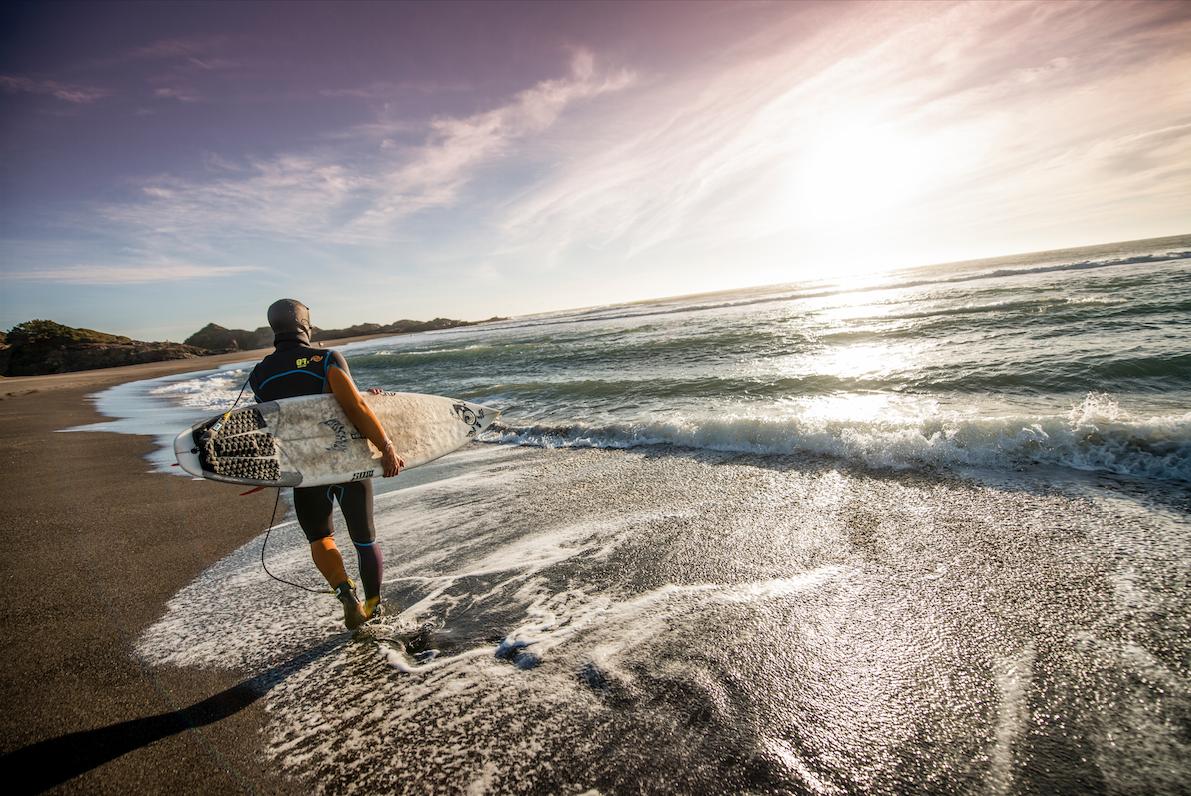 Imagen de surfista caminando por la orilla del mar en playa Pichilemu
