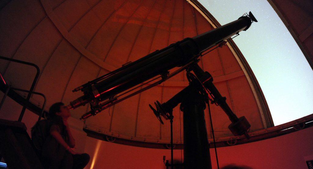 Imagen de una mujer mirando por uno de los telescopios del observatorio Cerro Calán