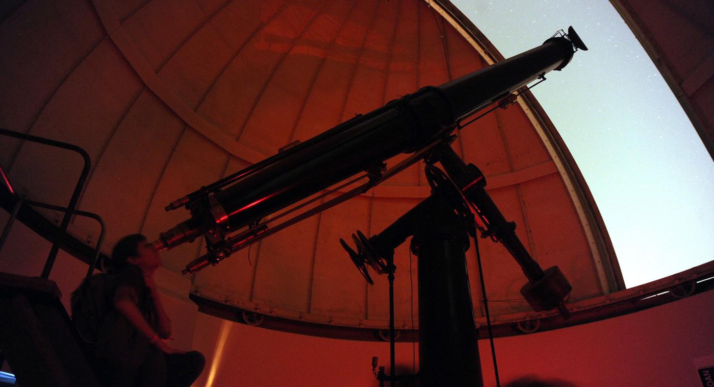 Imagen de una mujer mirando por los telescopios del observatorio de Cerro Calán