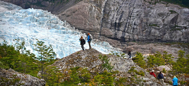 Vista panorámica del Glaciar Serrano, donde se aprecia a dos turistas admirando las bellezas del lugar