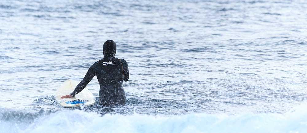 Imagen de surfista entrando al mar con su tabla de surf en el brazo