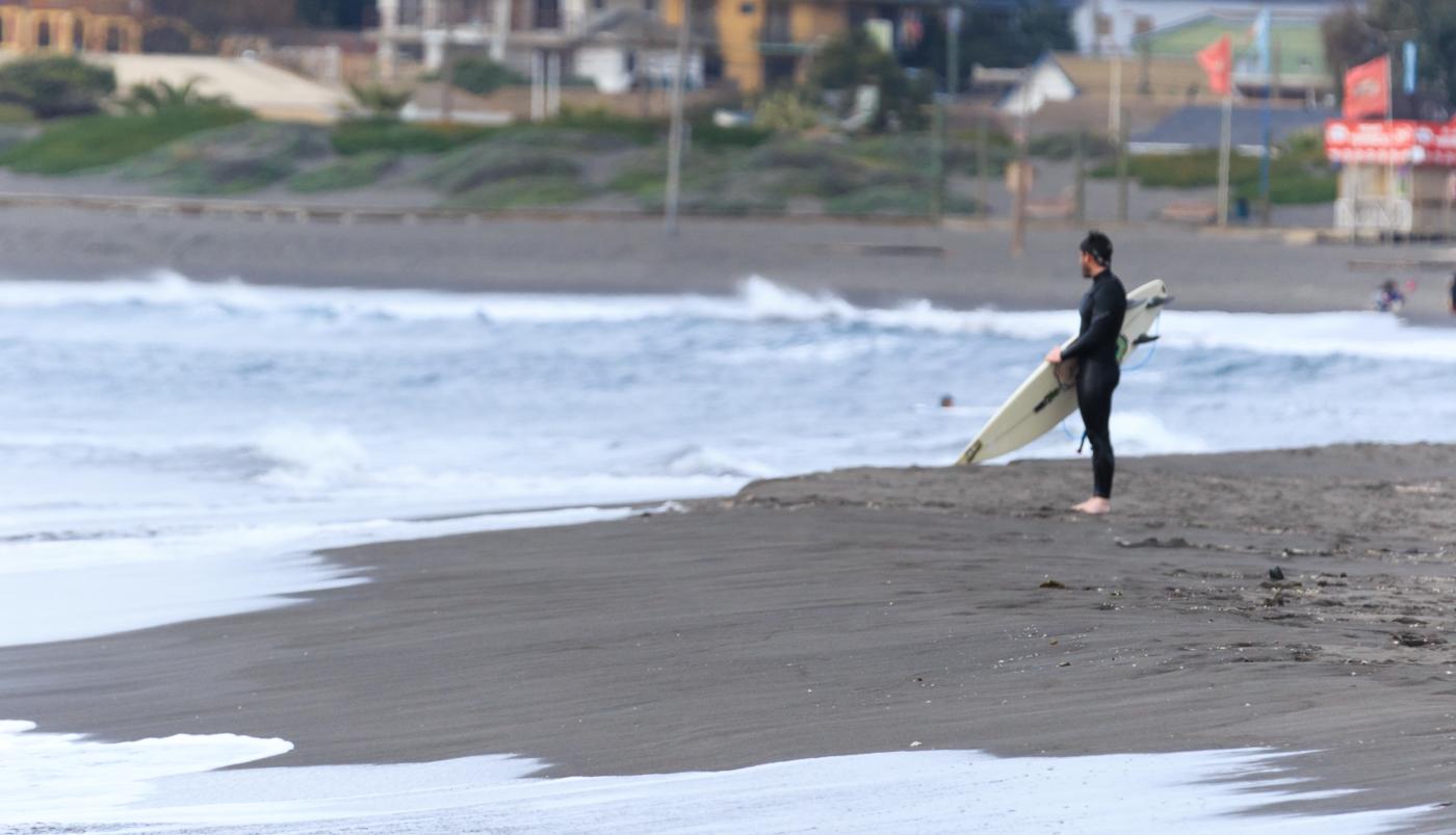 Imagen de surfista a la orilla del mar esperando una ola en la playa de Pichilemu