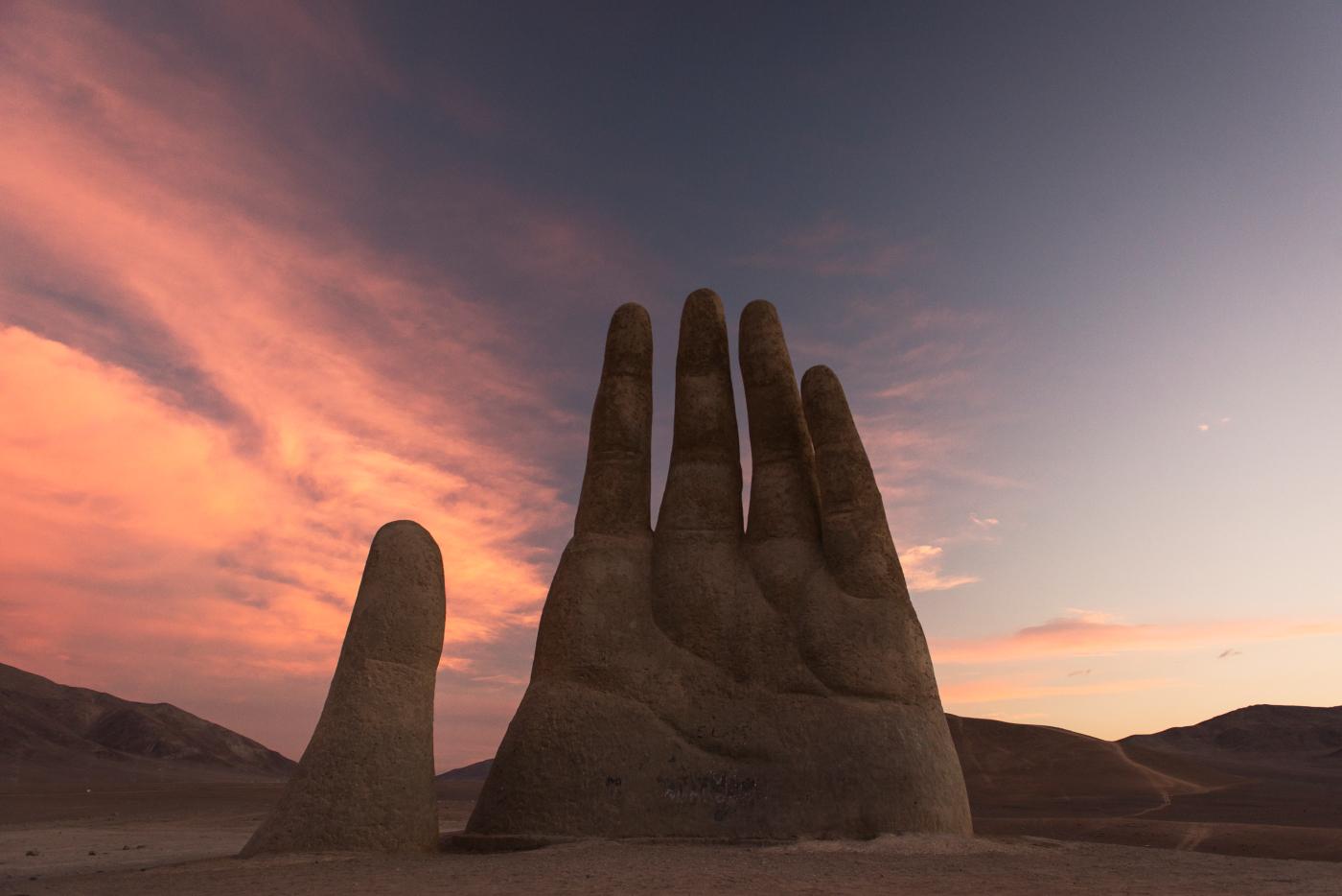 Imagen de la escultura que imita una manos sepultada en medio del Desierto de Atacama