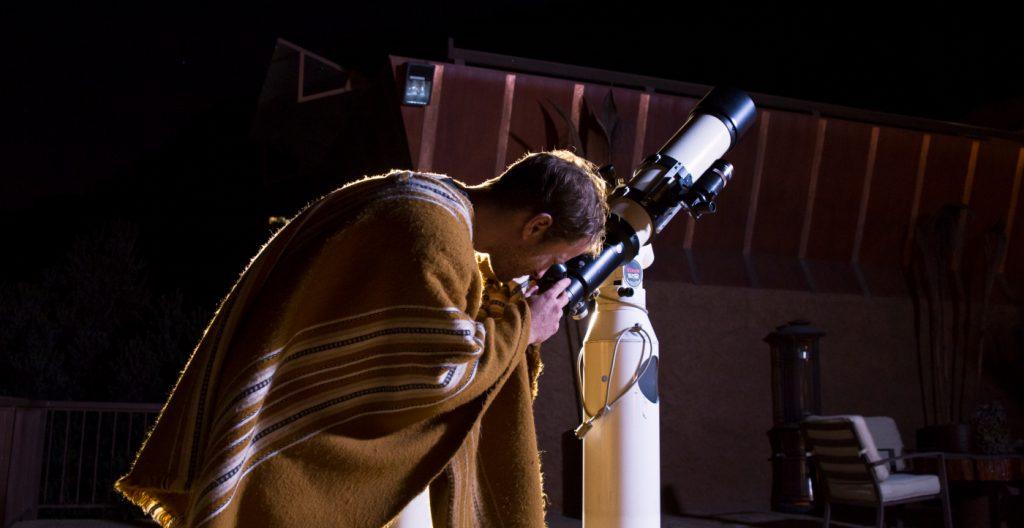 Fotografía de un turista mirando las estrellas con un telescopio en el Cajón del Maipo