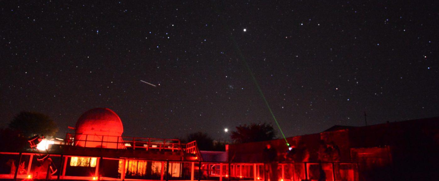 Imagen panorámica nocturna del Observatorio Alarkapin bajo un cielo estrellado que hace resaltar las luces de las antenas de la instalación.