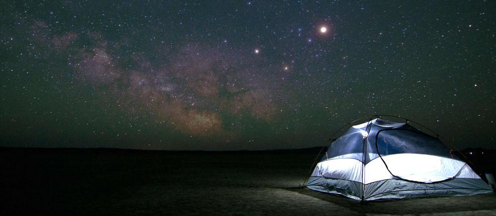 Imagen nocturna de una carpa iluminada por el cielo estrellado