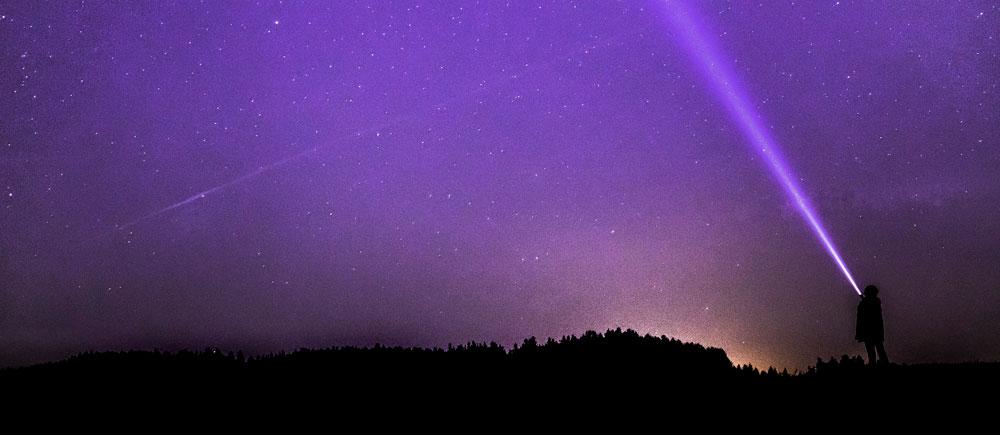 Imagen nocturna de una persona apuntando al cielo con una linterna en búsqueda de avistamientos de OVNIS en Chile