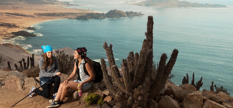 Imagen de unas turistas descansando luego de un trekking en uno de los miradores del Parque Nacional Pan de Azúcar