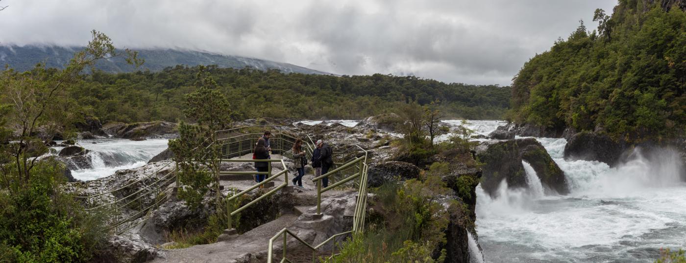 Imagen de unos turistas recorriendo los senderos guiados en medio de cascadas de agua en el Parque Nacional Vicente Perez Rosales