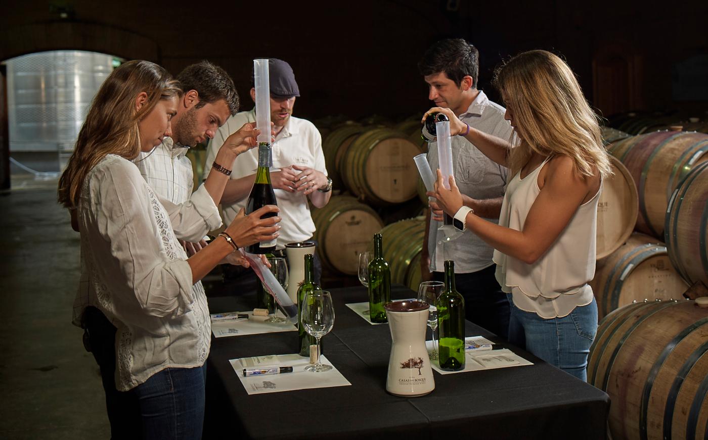 Imagen de un grupo de turistas realizando una cata de vino profesional en medio de un sala de barricas de la viña chilena Santa Carolina.
