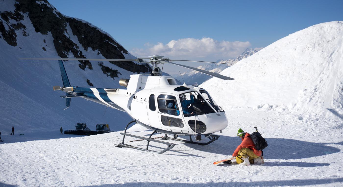 Imagen de la cima de la cordillera nevada donde un helicoptero está dejando a un deportista que se deslizará desde la cumbre
