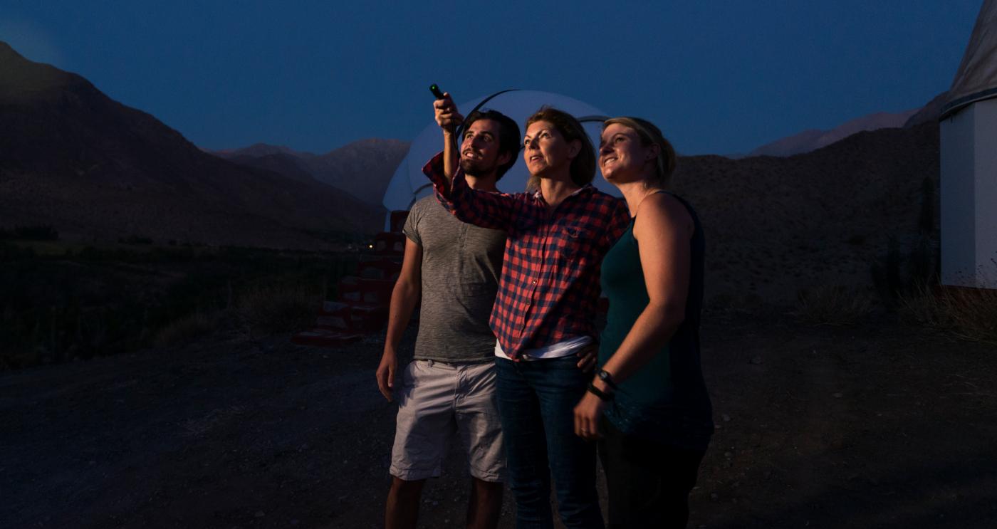 Imagen nocturna de tres turistas observando las estrellas a ojo desnudo en uno de los observatorios del norte de Chile