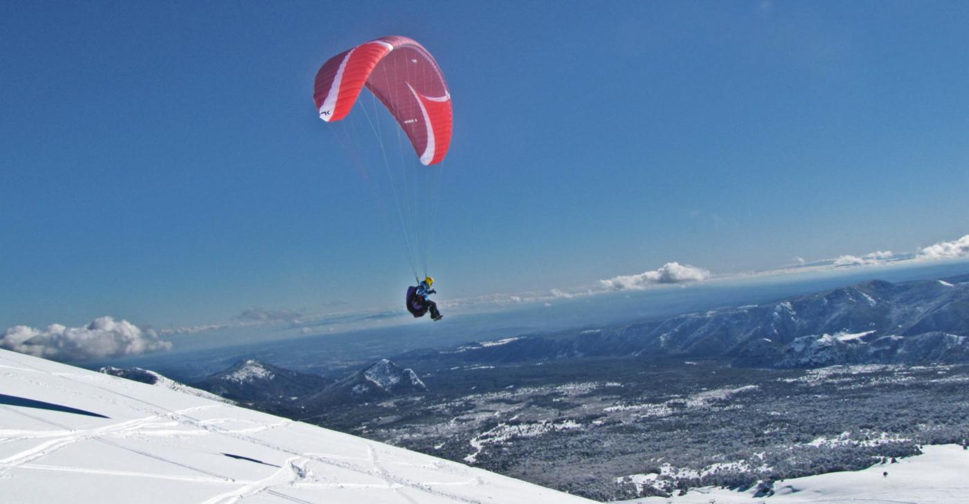 Imagen del vuelo en parapente de un deportista en las cumbres nevadas que rodean el Centro de Ski Las Araucarias