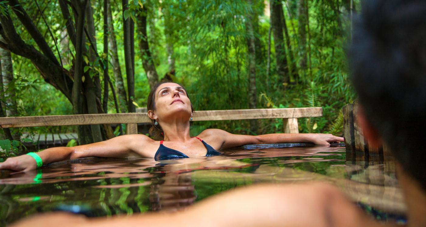 Imagen de una mujer muy relajada disfrutando al interior de una tina caliente de madera en medio de la naturaleza