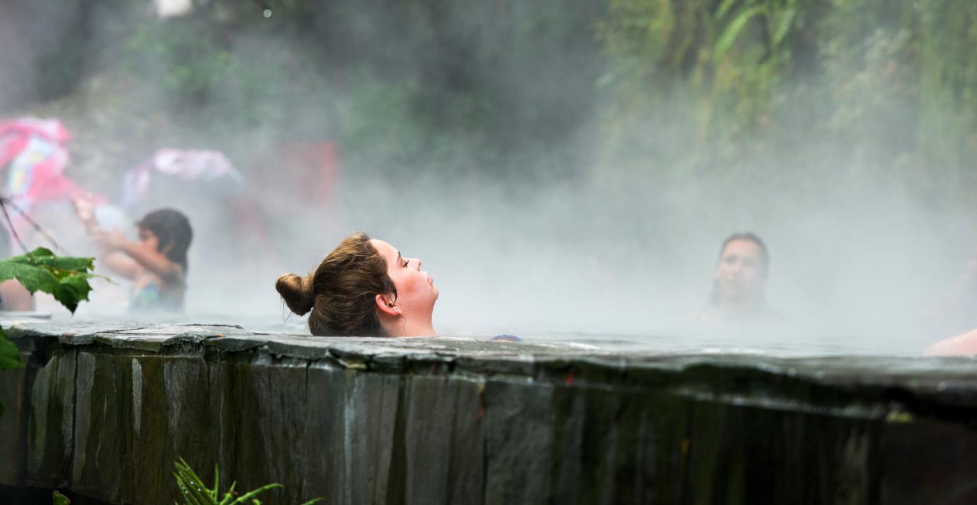 Imagen de una mujer descansando y disfrutando de los beneficios de las fuentes termales en Chile, donde se puede ver como sale vapor de la piscina termal instalada en medio de la naturaleza