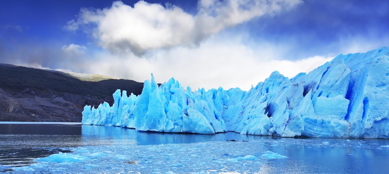 Imagen impactante del glaciar Grey en la Patagonia chilena, donde se ve el azul de los hielos eternos en contraste con las nubes blancas y el cielo despejado.
