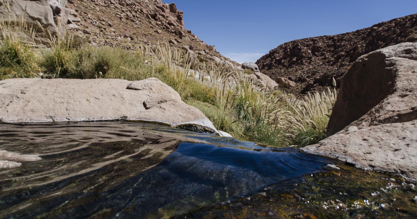 Imagen de las aguas prístinas de las Termas de Puritama, piscina natura en medio de un ambiente rocoso y rodeado de montañas