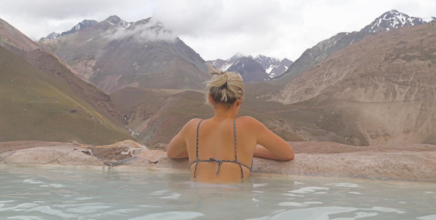 Fotografía que muestra a una turista sumergida en uno de las fuentes termales de las Termas del Plomo, admirando el paisaje rodeado de montañas.