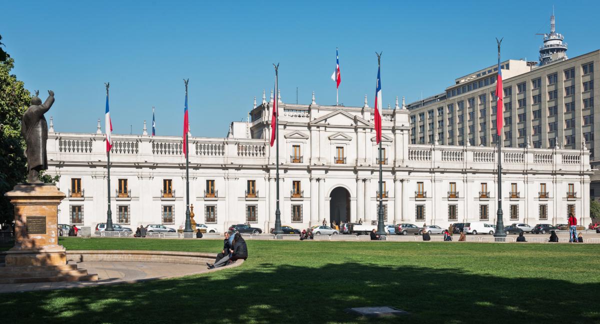 Imagen del Palacio de La Moneda en un hermoso día soleado donde destacan banderas chilenas que la rodean