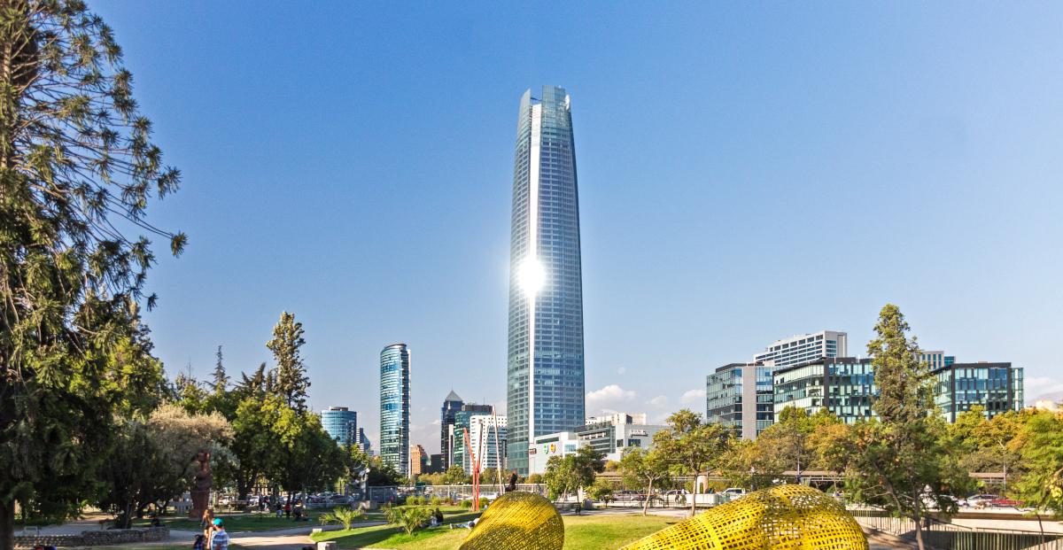 Imagen panorámica del edifico Costanera Center y los edificios en altura que lo rodean, con una mirada desde el parque aledaño en un día muy soleado