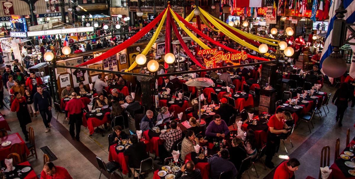 Imagen del interior del Mercado Central de Santiago, donde se ve las mesas de los puestos de comida llenos de gente disfrutando platos típicos