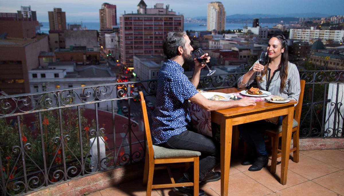 Imagen de una pareja disfrutando de una copa de vino y gastronomia chilena en una terraza de Valparaíso