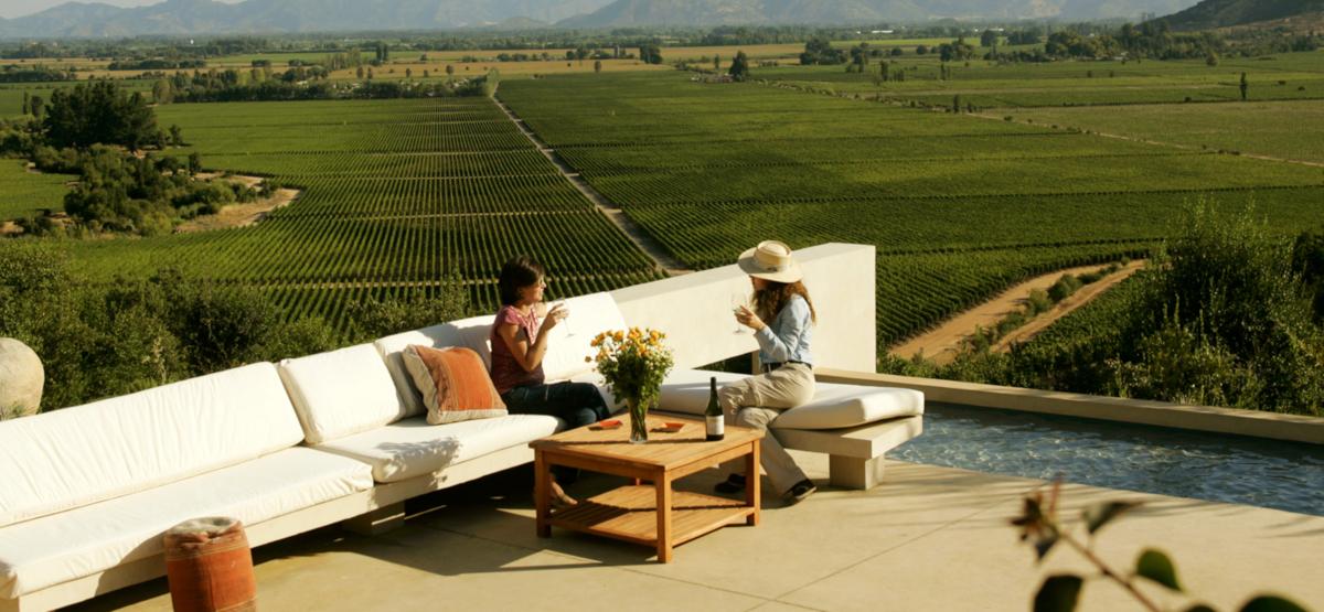 Imagen de dos mujeres degustando una copa de vino chileno en medio del Valle de Apalta