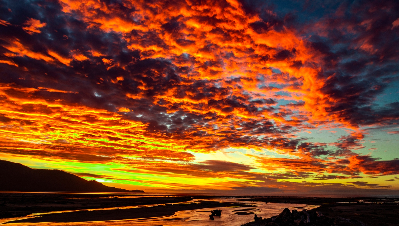 Imagen del Parque Nacional Corcovado en un hermoso atardecer que tiñe de colores cobres sus cielos, aguas y montañas