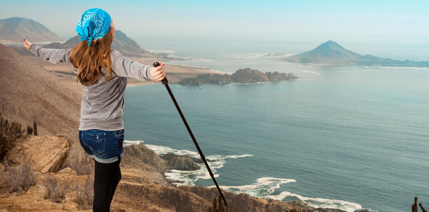 Mirador Parque Nacional Pan de Azucar donde se ve una mujer con los brazos abiertos disfrutando el paisaje