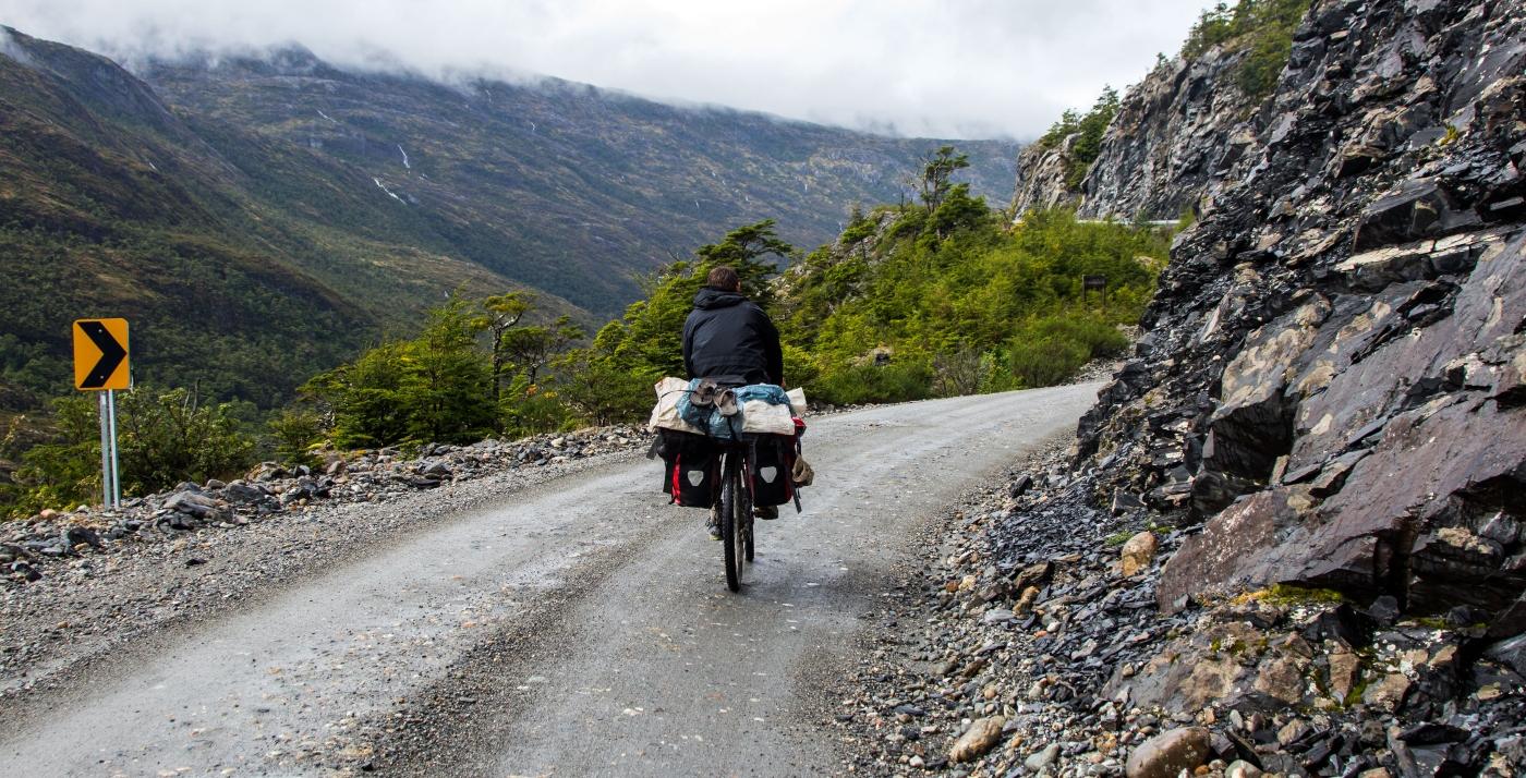 Imagen de un hombre recorriendo la Carretera Austral en bicicleta, donde se ve el camio en buen estado