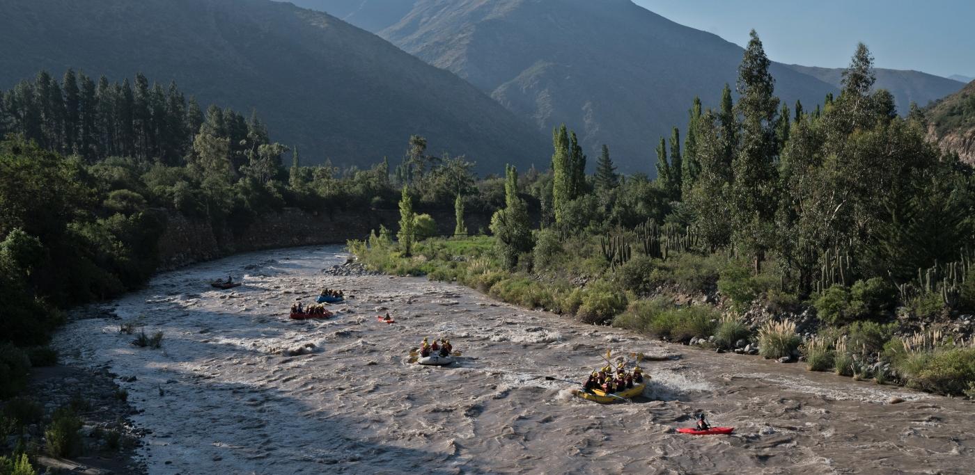 Imagen de un grupo d epersonas realizando rafting en el río del Cajón del Maipo en un día de otoño