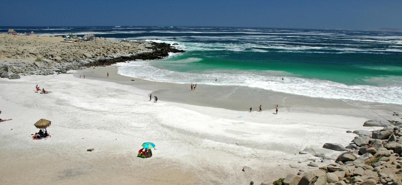 Imagen panorámica de Playa La Virgen donde se luce sus aguas limpias y arenas blancas