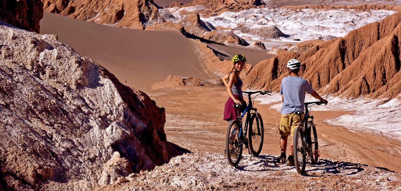 Imagen de una pareja de turistas recorriendo San Pedro de Atacama en bicicleta