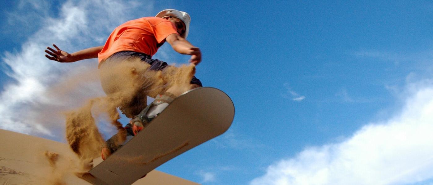 imagen de un hombre realizando sandboard por las dunas del Desierto de Atacama