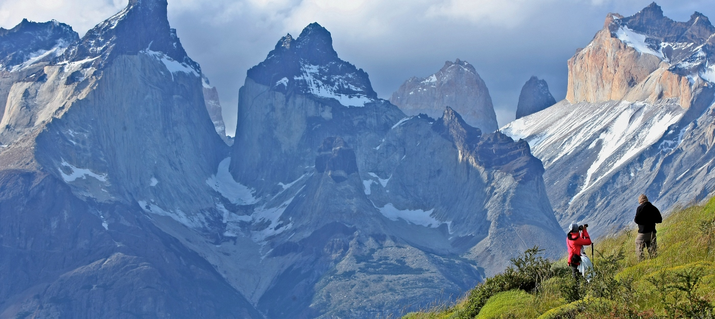 Imagen de los cuernos de las Torres del Paine donde destacan dos turistas fotografiando el paisaje