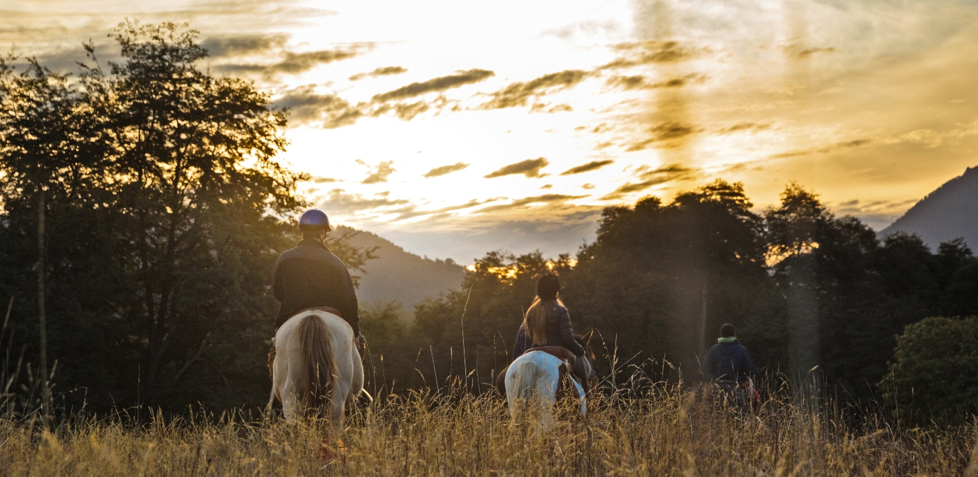 Imagen de una pareja cabalgando por la reserva natural Huilo Huilo